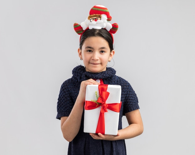 Happy and cheerful little girl in knit dress wearing red tie with funny christmas rim on head holding christmas present looking with smile on face