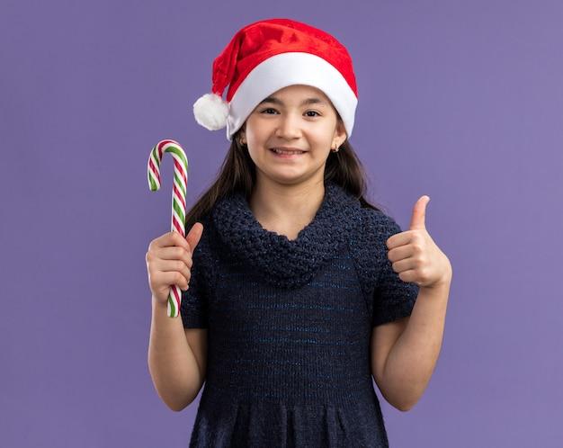 Bambina felice e allegra in abito a maglia che indossa un cappello da babbo natale che tiene in mano un bastoncino di zucchero con un sorriso sul viso che mostra i pollici in su in piedi sul muro viola