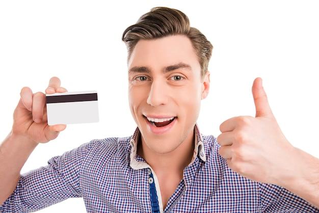 Счастливый веселый человек держит банковскую карту и показывает палец вверх