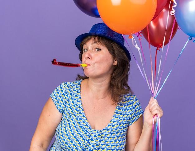 Felice e allegra donna di mezza età con cappello da festa che tiene un mazzo di palloncini colorati che soffia un fischietto che celebra la festa di compleanno in piedi sopra il muro viola