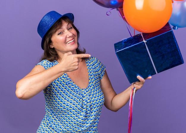 Felice e allegra donna di mezza età con cappello da festa che tiene un mazzo di palloncini colorati e presente che punta con il dito indice sorridendo festeggiando la festa di compleanno in piedi sul muro viola