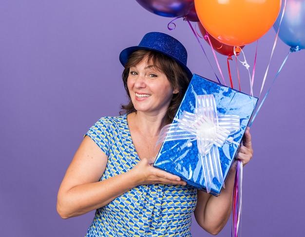 Felice e allegra donna di mezza età con un cappello da festa che tiene in mano un mazzo di palloncini colorati e presenta presentandolo con un braccio sorridente