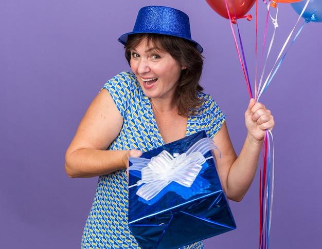 Felice e allegra donna di mezza età con cappello da festa che tiene in mano un mazzo di palloncini colorati e presente sorridente che celebra ampiamente la festa di compleanno in piedi sul muro viola