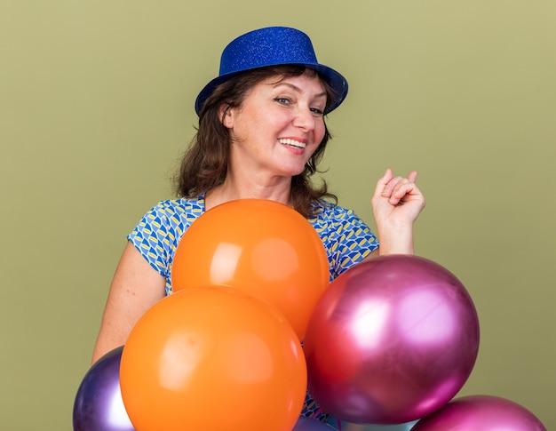 Felice e allegra donna di mezza età con cappello da festa che tiene in mano un mazzo di palloncini colorati sorridenti che celebrano ampiamente la festa di compleanno in piedi sul muro verde green