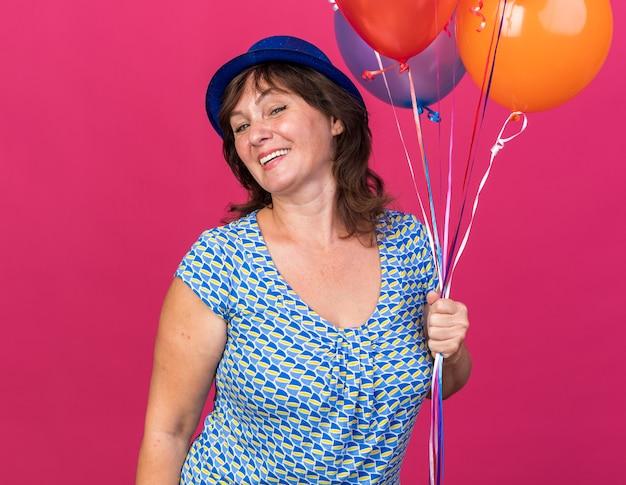 Felice e allegra donna di mezza età con cappello da festa che tiene in mano un mazzo di palloncini colorati sorridenti che celebrano ampiamente la festa di compleanno in piedi sul muro rosa