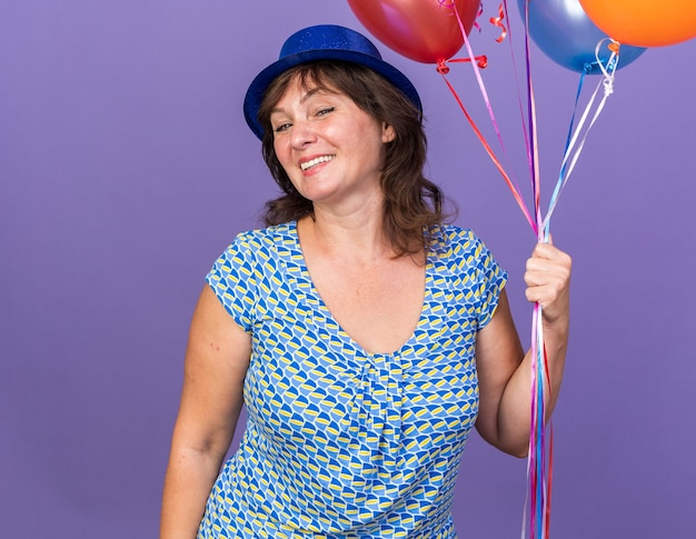 Felice e allegra donna di mezza età con cappello da festa che tiene in mano un mazzo di palloncini colorati sorridenti che celebrano ampiamente la festa di compleanno in piedi sul muro viola purple