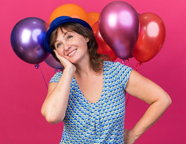 Felice e allegra donna di mezza età con cappello da festa che tiene palloncini colorati guardando in alto con un sorriso sul viso che celebra la festa di compleanno in piedi sul muro rosa
