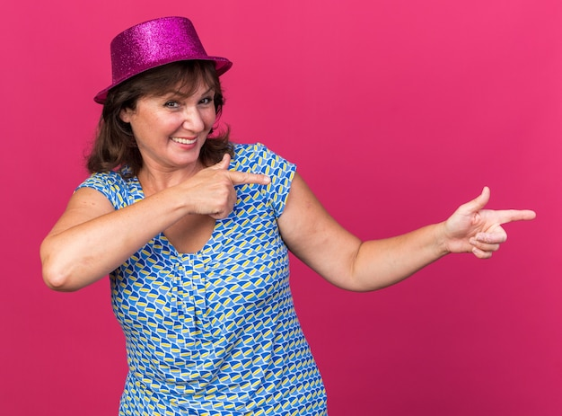Felice e allegra donna di mezza età con cappello da festa che punta con il dito indice verso il lato sorridendo ampiamente