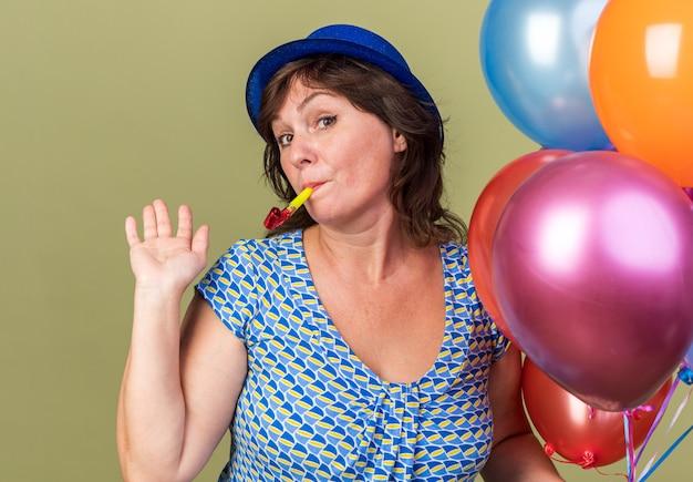 Felice e allegra donna di mezza età in cappello da festa con un mucchio di palloncini colorati che soffiano un fischietto