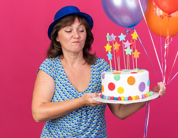 Happy and cheerful middle age woman in party hat with colorful balloons holding birthday cake looking at it with smile on face celebrating birthday party standing over pink wall