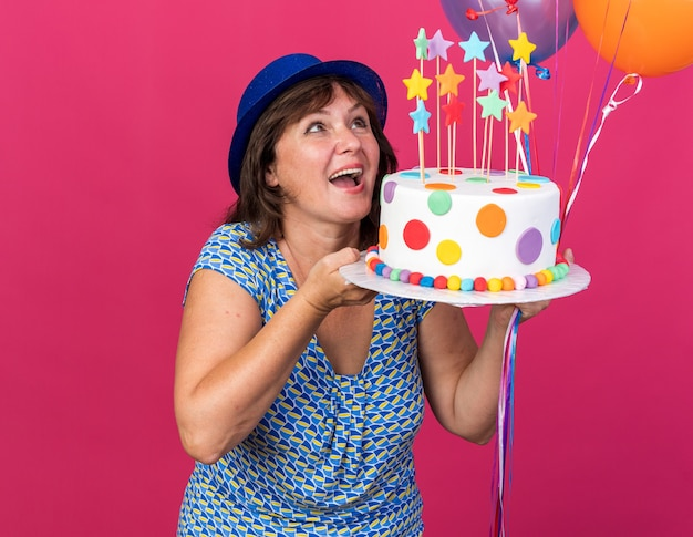 Happy and cheerful middle age woman in party hat with colorful balloons holding birthday cake looking up smiling broadly celebrating birthday party standing over pink wall