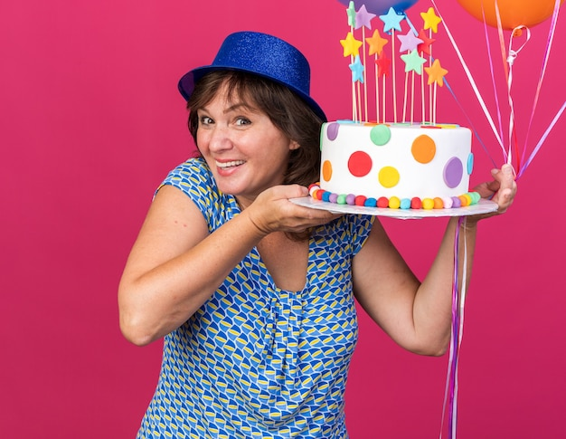 Happy and cheerful middle age woman in party hat with colorful balloons holding birthday cake  smiling broadly celebrating birthday party standing over pink wall
