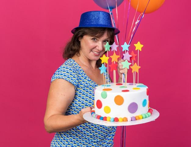 Felice e allegra donna di mezza età in cappello da festa con palloncini colorati che tengono torta di compleanno sorridendo ampiamente