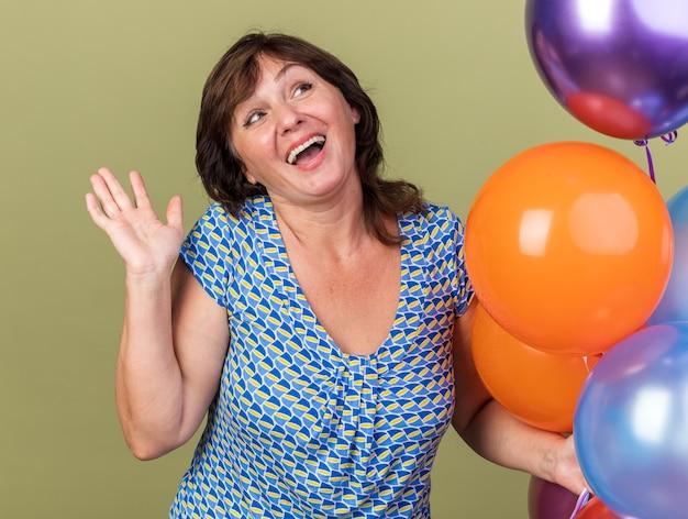 Felice e allegra donna di mezza età con un mazzo di palloncini colorati che guarda in alto sorridendo ampiamente con il braccio alzato