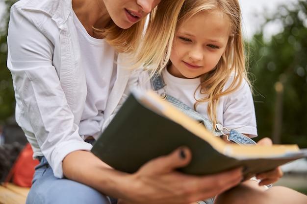 공주의 새로운 동화를 읽는 동안 공원에서 어머니와 함께 쉬고있는 행복한 쾌활한 미스