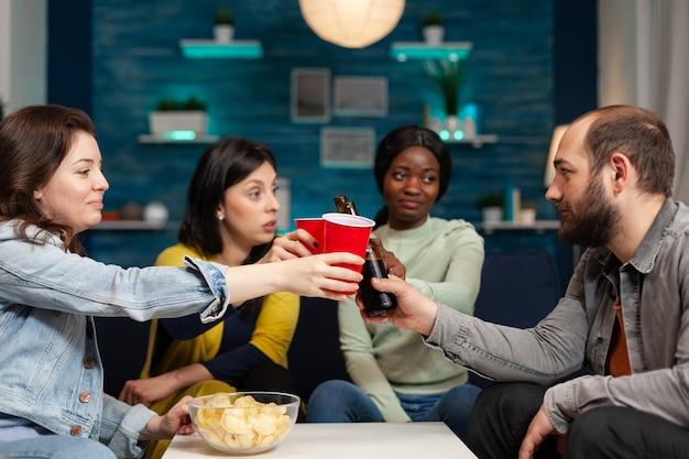 幸せで陽気な多民族の友人が楽しんで楽しんでいる間ビールをチリンと鳴らしている多民族の人々のグループは、リビングルームで夜遅くソファに座って一緒に時間を過ごします。