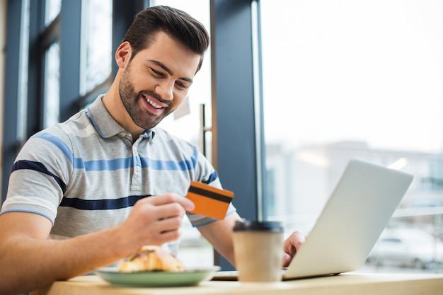 Счастливый веселый приятный человек улыбается и смотрит на свою кредитную карту, сидя перед ноутбуком