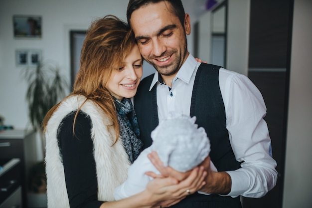행복한 쾌활한 부모가 작은 신생아를 봅니다.