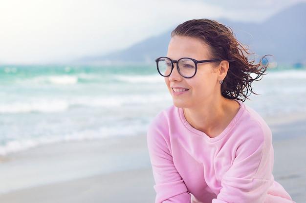 幸せな陽気な物思いにふける少女、笑みを浮かべて、素敵な天気を楽しんで、海のビーチを歩いて素敵な美しい女性。笑顔、遠くを見ている、夢を見ている大きなレンズとメガネのきれいな女性