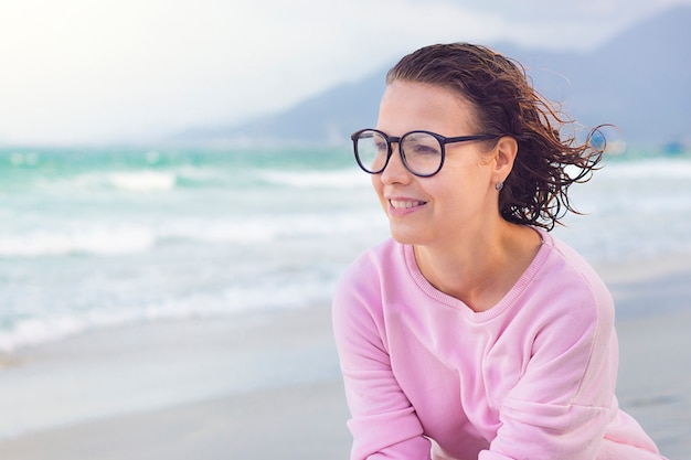 Happy cheerful pensive thoughtful girl, young nice beautiful woman smiling, enjoying good weather, walking at sea beach. pretty lady in glasses with big lenses smiling, looking into distance, dreaming