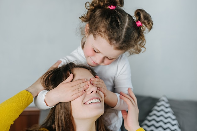 Happy cheerful preschooler daughter making surprise covering eyes to smiling mom sitting on bed at home. close up of cute little girl have fun playing with loving young mother spend time together