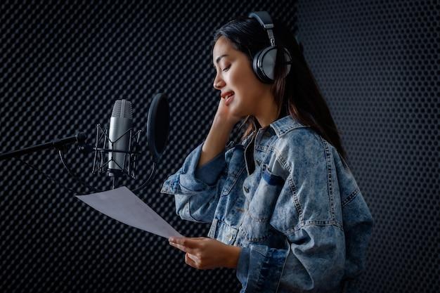 전문 스튜디오에서 마이크 앞에서 노래를 녹음하는 헤드폰을 끼고 있는 젊은 아시아 여성 보컬의 초상화를 행복하게 웃고 있습니다.
