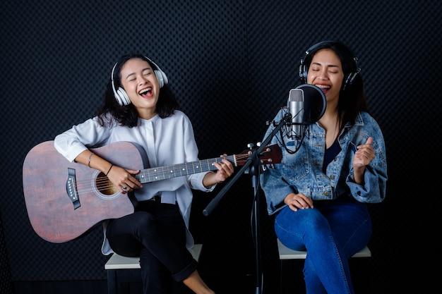 Счастливый веселый симпатичный улыбающийся портрет двух молодых азиатских вокалисток в наушниках с гитарой, записывающей песню перед микрофоном в профессиональной студии
