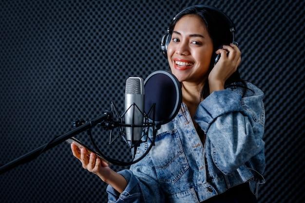 若いアジアの女性の肖像画の幸せで陽気なかわいい笑顔は、プロのスタジオでマイクの前に歌を録音しているスマートフォンのボーカリストwearingheadphonesを見てください