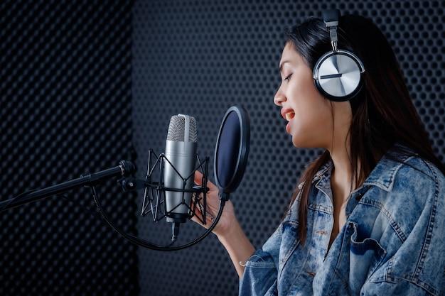 전문 스튜디오에서 마이크 앞에서 노래를 녹음하는 헤드폰을 끼고 있는 스마트폰 보컬리스트를 바라보는 젊은 아시아 여성의 행복한 미소