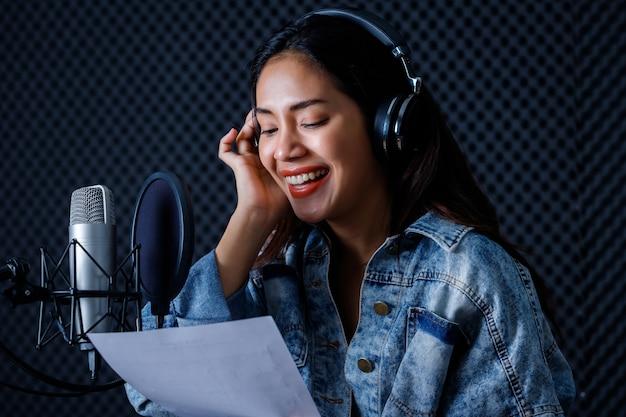 プロのスタジオでマイクの前で歌を録音するヘッドフォンを身に着けている若いアジアの女性ボーカリストの肖像画の幸せな陽気なかわいい笑顔