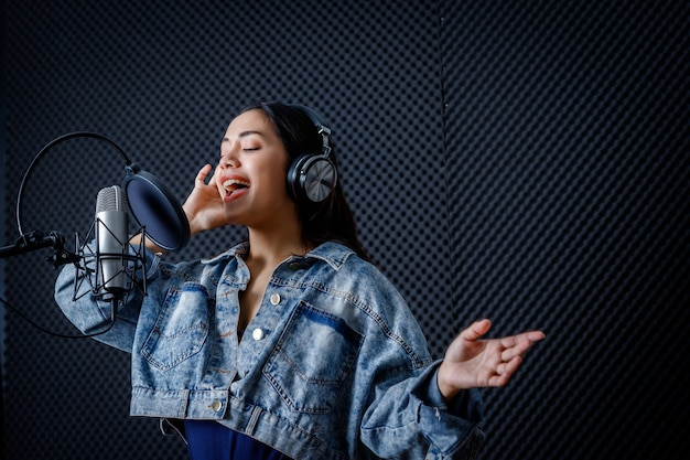 Счастливый веселый симпатичный улыбающийся портрет молодой азиатской женщины-вокалиста в наушниках, записывающий песню перед микрофоном в профессиональной студии