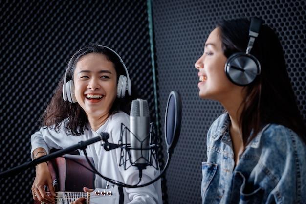 Счастливый веселый симпатичный улыбающийся портрета два молодых азиатских вокалиста в наушниках с гитарой записывают песню перед микрофоном в профессиональной студии