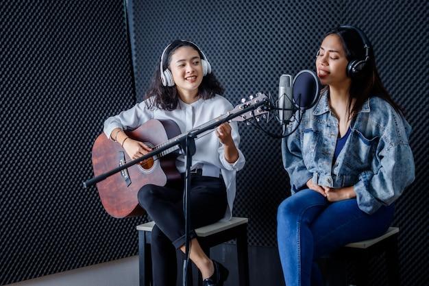 肖像画の幸せな陽気なかわいい笑顔プロのスタジオでマイクの前に歌を録音するギターとヘッドフォンを身に着けている2人の若いアジアの女性ボーカリスト