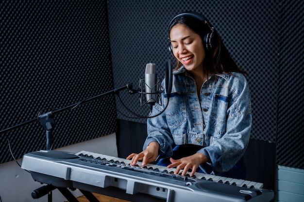プロのスタジオで彼女のバンドのリハーサル中にマイクの前で曲を録音し、キーボードを演奏するヘッドフォンを身に着けている若いアジアの女性ボーカリストの幸せで陽気なかわいい笑顔