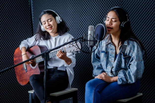 Happy cheerful pretty smiling of portrait two young asian woman vocalist wearing headphones with a guitar recording a song front of microphone in a professional studio