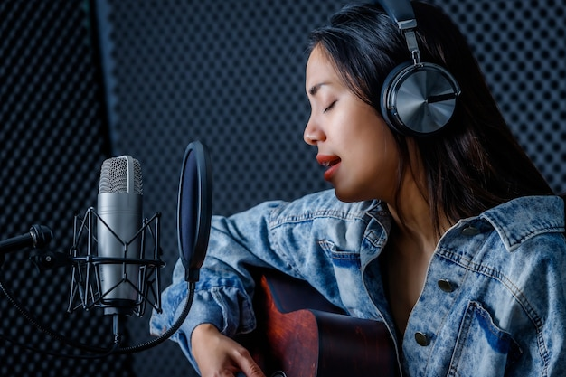 Happy cheerful pretty smiling of portrait a young asian woman vocalist wearing headphones with a guitar recording a song front of microphone in a professional studio