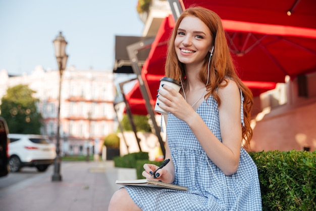 Счастливый веселый рыжий девушка в наушниках