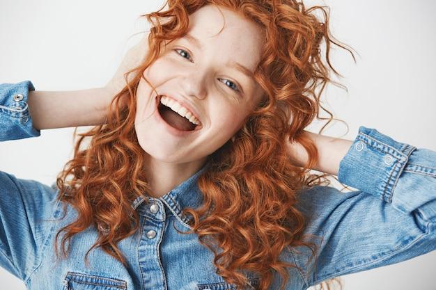 Счастливый веселый рыжий девушка улыбается, радуясь с раскрытой пасти.