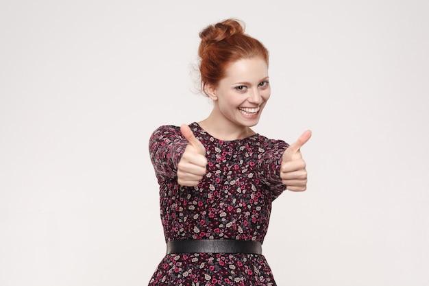 Счастливая веселая рыжая женщина показывает палец вверх и зубастую улыбку. изолированные студия выстрел на сером фоне