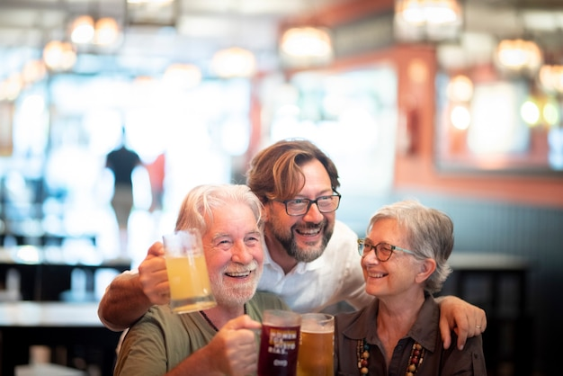 レストランで一緒にビールを飲みながら楽しんでいる息子、後ろから母と父を抱きしめる息子との幸せな陽気な先輩家族。飲み物を楽しんだり、レストランで祝う楽しい家族