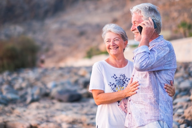 Happy and cheerful senior old caucasian couple in love and relationship enjoying together the outdoor leisure activity talking with the phone and looking around