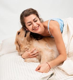 幸せな陽気な笑顔の女性が遊んで、自宅のベッドで彼女の犬とハグ