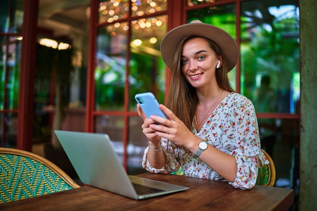 Happy cheerful smiling beautiful cute joyful young freelancer girl wearing wireless headphones using laptop and phone for remote work and online browsing at green cafe