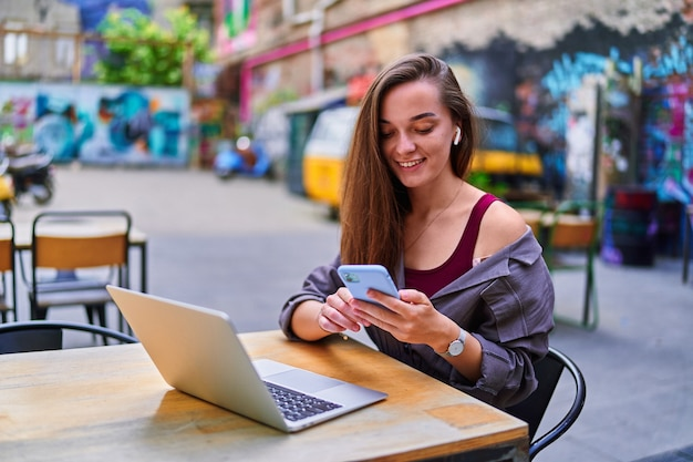 Happy cheerful smiling beautiful cute joyful young millennial freelancer girl wearing wireless headphones using laptop and phone for remote work, social networking and online browsing at cafe