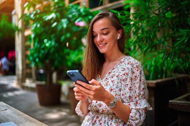 Счастливая веселая улыбающаяся красивая милая радостная молодая девушка-миллениал в беспроводных наушниках и по телефону в кафе