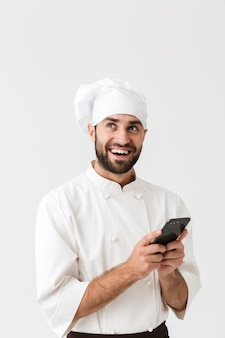 Happy cheerful smiling young chef posing in uniform using mobile phone.