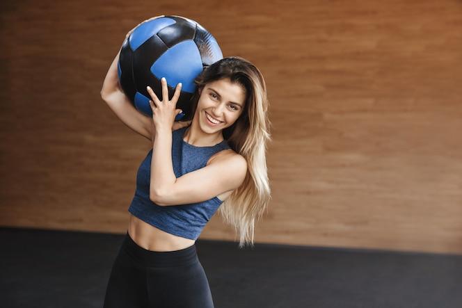 腹部の筋肉を持つ幸せで陽気な強いスポーツウーマンは、肩にクロスフィット薬のボールを運び、満足して笑っています。