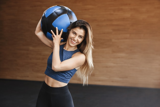 Happy cheerful strong sportswoman with abdominal muscles, carries crossfit medicine ball on shoulder, smiling pleased.