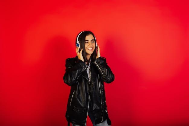 黒革のジャケットを着た幸せで陽気なスタイリッシュな女の子は、ワイヤレスヘッドフォンを着用し、お気に入りの曲を聴いて、赤い表面に隔離されています。