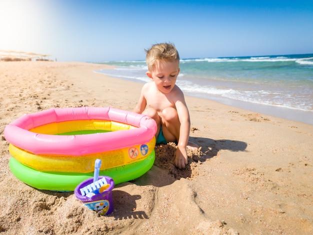 해변에서 모래를 파고 부풀릴 수 있는 수영장을 가지고 노는 행복한 쾌활한 투들러 소년. 여름 방학 동안 휴식을 취하고 좋은 시간을 보내는 어린이.